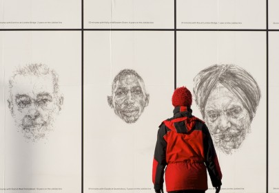 Individual looking at large pencil portraits