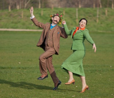 Still from film. Two characters in period costume skipping through field.