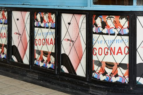 Lucy McKenzie, 'Everyone's Cognac (Advertising poster)' and 'Lipstick I (Advertising poster)', Sudbury Town Station, 2020. Commissioned by Art on the Underground. Photo: GG Archard, 2020