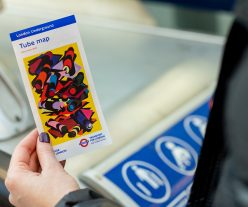 The 33rd edition of the pocket tube map cover by Phyllida Barlow, a bright yellow artwork overlaid with colourful geometric shapes mimicking tube tunnels, in the hand of a member of the public.